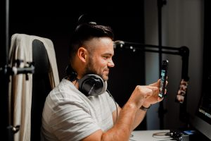 Guy looking at phone with headphones on
